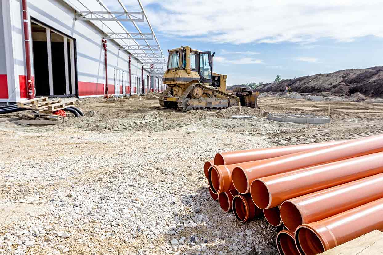Outside area construction with orange pipes and bulldozer